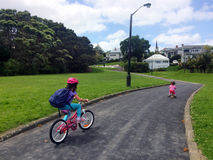 两个姐妹乘驾自行车在公园 库存图片