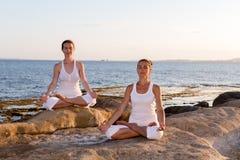 两个姐妹做着瑜伽锻炼在海滨 库存图片