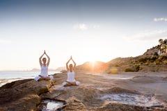 两个姐妹做着瑜伽锻炼在海滨 图库摄影