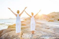 两个姐妹做着瑜伽锻炼在海滨 免版税图库摄影