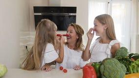 两个姐妹和他们的母亲获得乐趣用辣椒在家在厨房 女孩做有红色的一根髭 股票视频