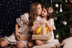 两个姐妹在圣诞树附近分享礼物 图库摄影