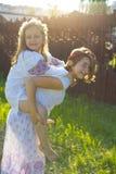 两个姐妹在草坪嬉戏在夏天 免版税图库摄影