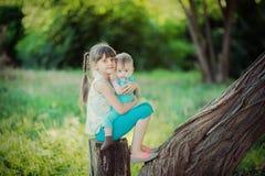 两个姐妹坐一个树桩在一个美丽的公园在夏天 库存图片