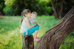 两个姐妹坐一个树桩在一个美丽的公园在夏天 免版税库存照片