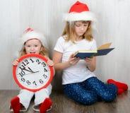 两个姐妹坐在圣诞老人帽子的地板 库存图片