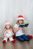 两个姐妹坐在圣诞老人帽子的地板 免版税库存照片