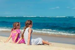两个姐妹坐海滩和神色在海洋 库存图片