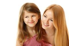 两个姐妹愉快的微笑的孩子和青少年的看的t画象  图库摄影