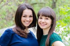 两个姐妹或女朋友微笑,笑和拥抱户外在春天或夏天 免版税库存照片