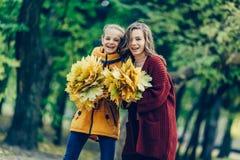 两个姐妹拥抱,与一束叶子在公园 库存照片