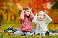 两个姐妹获得乐趣一起在秋天公园 图库摄影