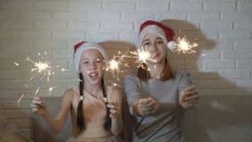 两个姐妹,一女孩和一个少年,拿着被点燃的闪烁发光物在他们的手上的圣诞老人的帽子的,挥动他们和微笑 股票录像