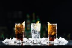 两个威士忌酒和焦炭鸡尾酒和一白色酒精饮料在酒吧桌上 免版税库存照片