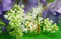 两个婚戒和白色淡紫色和紫色小苍兰婚礼花束  图库摄影