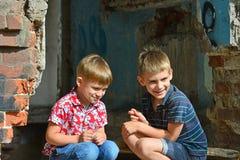 两个孤儿留给无家可归和坐在大厦的废墟附近由于一次军事冲突、火和earthq 库存图片