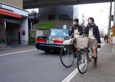 两个学校女孩在路循环在京都,日本 库存照片