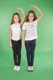 两个学校女孩握在头和测量他的成长上的手 库存照片