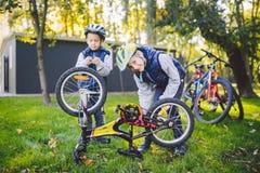 两个孩子、更老的学会修理自行车的男孩和弟弟 盔甲和唯一衣裳的两人兄弟姐妹使用泵浦工具 免版税库存照片