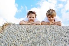 两个孩子、男孩和女孩传统巴法力亚服装的在麦田与干草捆 免版税图库摄影