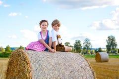 两个孩子、男孩和女孩传统巴法力亚服装的在麦田与干草捆 免版税库存图片