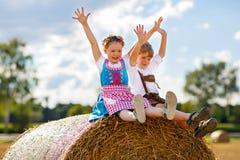 两个孩子、男孩和女孩传统巴法力亚服装的在麦田与干草捆 免版税库存照片