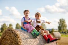 两个孩子、男孩和女孩传统巴法力亚服装的在麦田 免版税库存照片