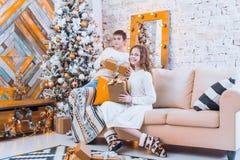两个孩子一个男孩和一个女孩一棵圣诞树的在一个沙发与 免版税库存照片