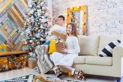 两个孩子一个男孩和一个女孩一棵圣诞树的在一个沙发有礼物的 在淡色 库存图片