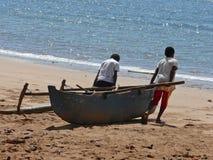 两个孩子乘在海滩的一个独木舟 免版税图库摄影