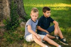 两个孩子充当公园 T恤杉和短裤的两个美丽的男孩有乐趣微笑 他们吃冰淇凌 免版税图库摄影