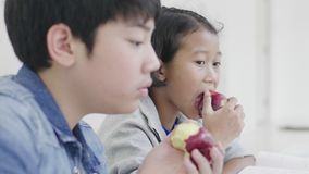 两个孩子吃着苹果 并且做家庭作业 股票录像