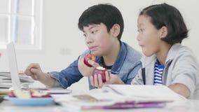 两个孩子吃着苹果 并且做家庭作业 股票视频