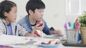 两个孩子吃着苹果 并且做家庭作业 影视素材