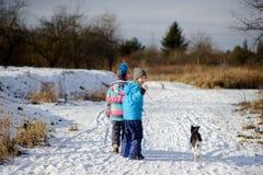 两个孩子和他们的狗在冬天步行 免版税库存图片