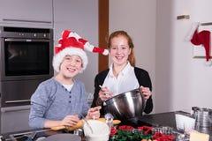 两个孩子在准备圣诞节面包店的厨房里 免版税库存照片