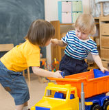 两个孩子在幼儿园相冲突或奋斗为玩具卡车 免版税图库摄影