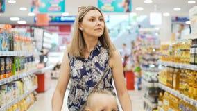 两个孩子在有妈咪的塑料户内购物推车市场 影视素材