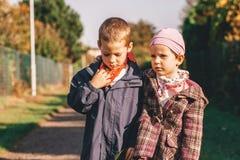 两个孩子在篱芭之间的道路中间站立在一冷的秋天天 免版税库存照片