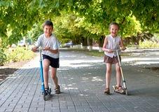 两个孩子在街道边路的滑行车乘坐在室外的城市,明亮的晴天 免版税库存图片