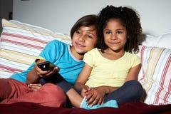 两个孩子坐一起看电视的沙发 库存照片