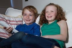 两个孩子坐一起看电视的沙发 免版税库存照片