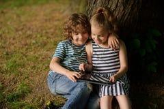 两个孩子坐在与看片剂屏幕的兴趣的更多树下 库存图片
