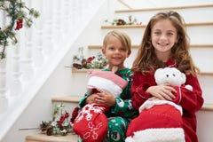 两个孩子坐在睡衣的台阶在圣诞节 免版税库存图片