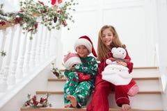 两个孩子坐在睡衣的台阶在圣诞节 免版税库存照片
