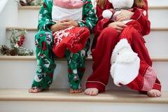 两个孩子坐有圣诞节长袜的台阶 免版税库存图片