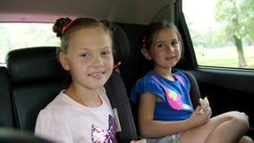两个孩子女孩在汽车的后座乘坐 他们中的一个在汽车座位,其他坐,更老的女孩附近坐 股票录像