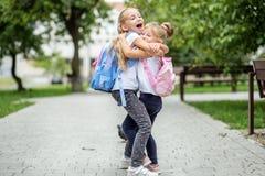 两个孩子拥抱和笑 学校的概念,研究,教育,友谊,童年 免版税库存图片