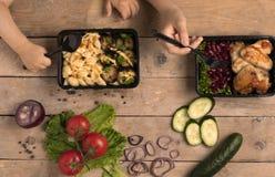 两个孩子拿着匙子和叉子在有烤鸡翅的食盒,蓝色毛巾下 免版税库存图片