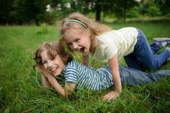 两个孩子是淘气的在绿草 库存照片